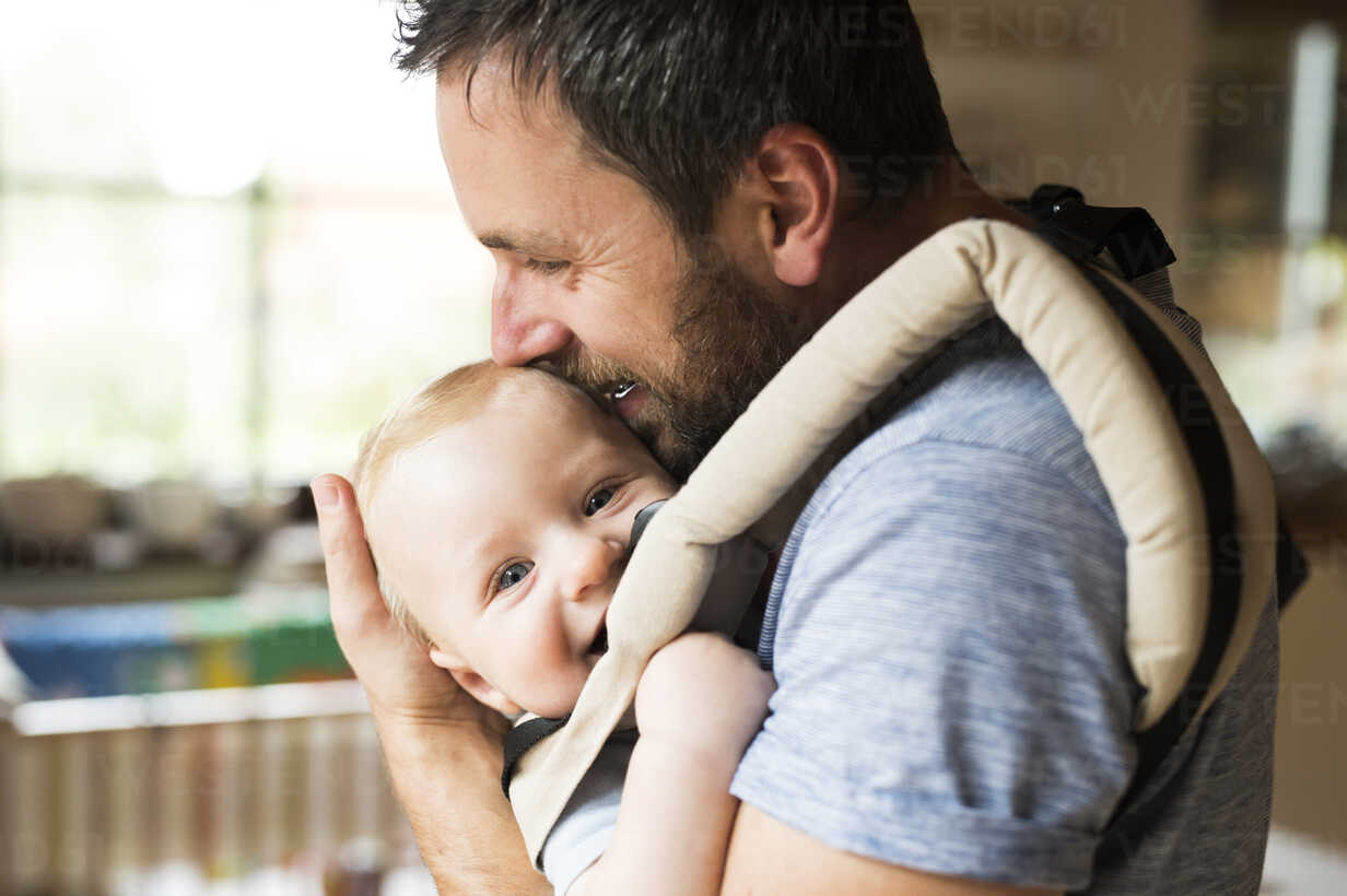 Happy father with baby in baby carrier at home - HAPF01227 - HalfPoint/Westend61