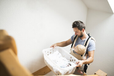 Father with baby in baby carrier carrying laundry basket walking upstairs - HAPF01230