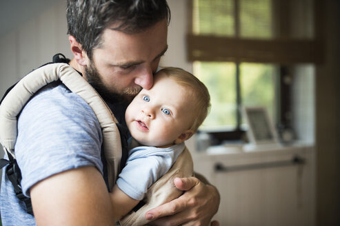 Father cuddling with baby in baby carrier - HAPF01233