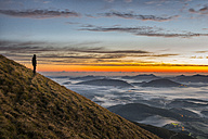 Italy, Umbria, Apennines, hiker  standing on Monte Acuto watching sunrise - LOMF00452