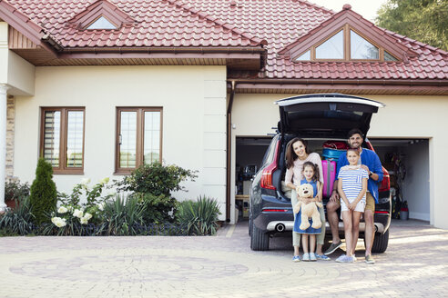 Happy family standing in front of car packed for vacation - WEST22307