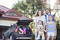 Happy family standing in front of car packed for vacation - WEST22310