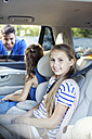Father standing at car window, talking to his daughters sitting in back seat - WEST22313