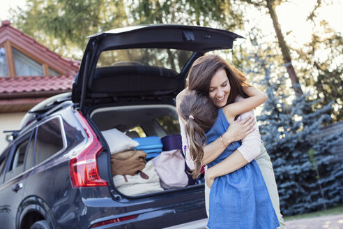 Mother and daughter embracing in front of their car - WEST22322