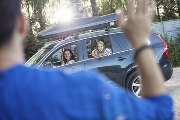 Father waving mother and daughter goodbye, as they drive off - WEST22328
