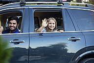 Father and daughter waving goodbye as the drive off in car - WEST22337