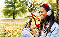 Young woman listening to music with her smartphone in a park in autumn - MGOF02707