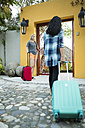 Two women arriving at vacation resort - ABAF02100