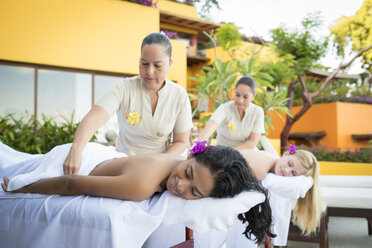 Two young women receiving a massage at a luxury vacation retreat - ABAF02103