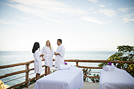 Vacation guests waiting for their outdoor massage on ocean front terrace of a luxury vacation resort - ABAF02106
