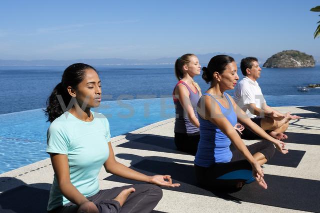 Yoga group exercising at ocean front resort - ABAF02109 - André Babiak/Westend61