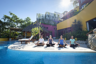 Yoga group exercising at ocean front villa - ABAF02112