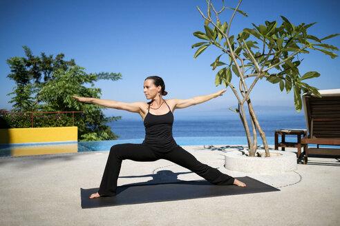 Woman practicing yoga at ocean front resort - ABAF02115