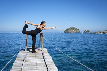 Woman practicing yoga on small dock at the cean - ABAF02118
