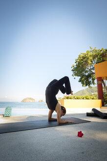 Woman practicing yoga at ocean front resort - ABAF02121