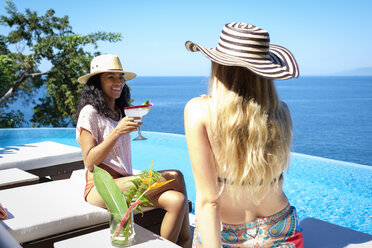 Two women enjoying cocktails at ocean front infinity swimming pool - ABAF02124