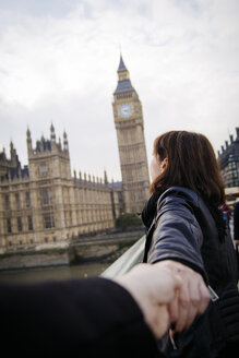 UK, London, woman pulling friend towards Big Ben - JPSF00025