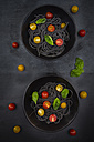 Two bowls of Spaghetti al Nero di Seppia with tomatoes and basil leaves - LVF05717