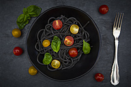 Bowl of Spaghetti al Nero di Seppia with tomatoes and basil leaves - LVF05720