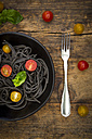 Bowl of Spaghetti al Nero di Seppia with tomatoes and fork on wood - LVF05726