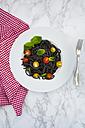 Plate of Spaghetti al Nero di Seppia with tomatoes and basil leaves - LVF05729