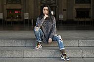 Young woman sitting on stairs shushing - KKAF00193