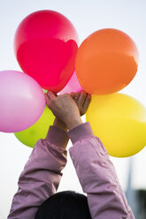 Woman holding balloons outdoors - KKAF00205