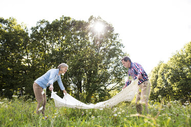 Senior couple spreading out blanket on a meadow - HAPF01237