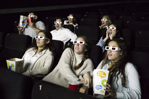 Scared people with 3d glasses watching a movie in a cinema - ABZF01637