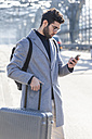 Businessman with baggage looking at cell phone - TCF05243