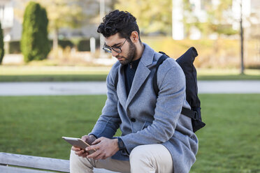 Young man sitting on bench using mini tablet - TCF05246