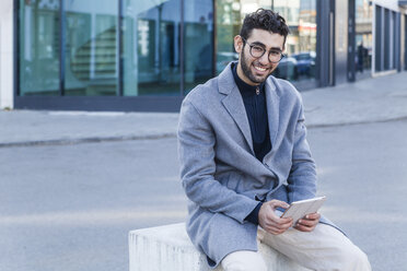 Portrait of smiling young man with mini tablet sitting on bollard - TCF05249