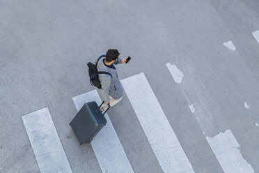 Businessman with baggage crossing the street while looking at cell phone, top view - TCF05252