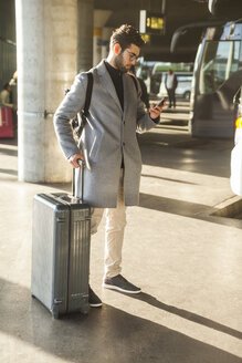 Businessman with baggage standing at bus terminal looking at cell phone - TCF05255