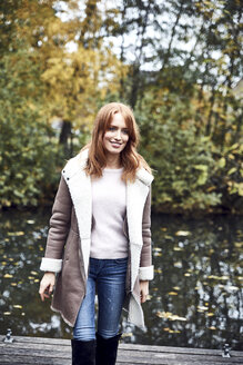 Portrait of smiling woman on jetty in autumn - SRYF00141