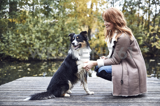 Smiling woman with her dog on jetty in autumn - SRYF00144 - Martina Ferrari/Westend61