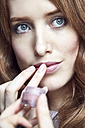 Portrait of redheaded woman applying cream on her lips - SRYF00147
