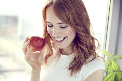 Portrait of redheaded woman with red apple - SRYF00150