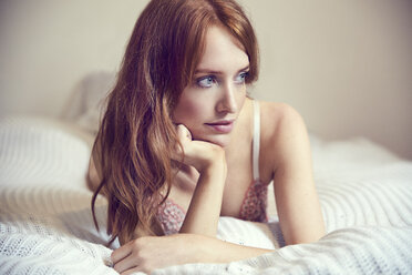Portrait of redheaded woman  wearing lingerie lying on bed - SRYF00162
