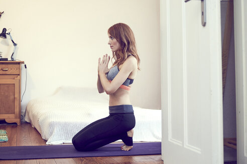 Redheaded woman doing yoga exercise at home - SRYF00174