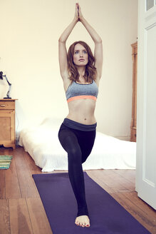 Redheaded woman doing yoga exercise at home - SRYF00177