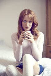 Portrait of redheaded woman with cup sitting on bed - SRYF00183