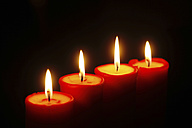 Row of four lighted red candles - JTF00792