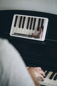 Man learning playing piano with video tutorial on a tablet - JPSF00031