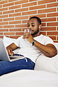 Young man with earphones sitting on bed using laptop - VABF00937