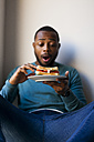 Young man eating a club sandwich - VABF00949