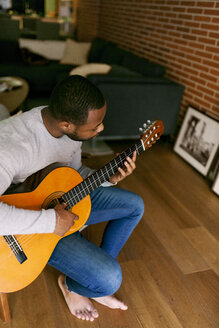 Young man at home playing guitar - VABF00958