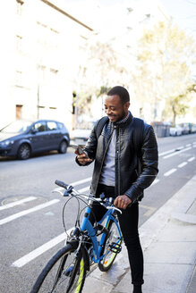 Smiling young man with bicycle checking his smartphone - VABF00961