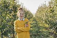Portrait of smiling young woman apple orchard - KNSF00730