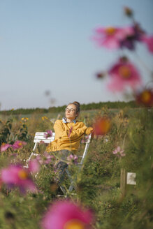 Young woman relaxing in cottage garden - KNSF00748
